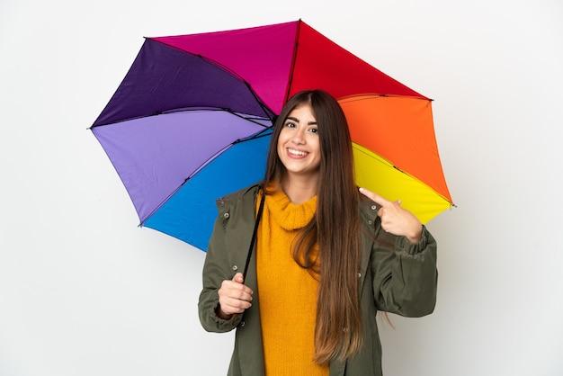 제스처를 엄지 손가락을주는 흰색 배경에 고립 된 우산을 들고 젊은 여자