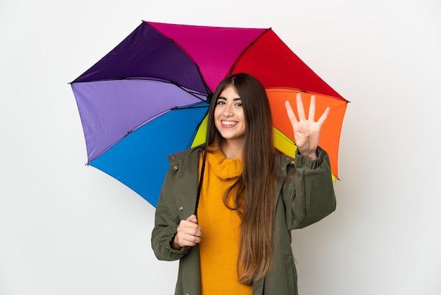 Молодая женщина, держащая зонтик на белом фоне счастлива и считая четыре пальцами