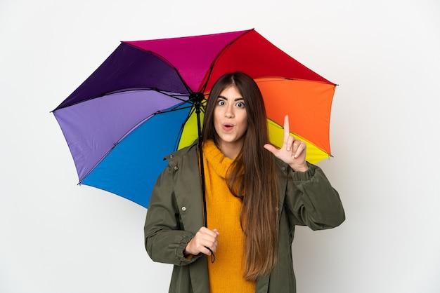 Молодая женщина, держащая зонтик на белом фоне, намереваясь реализовать решение, подняв палец вверх
