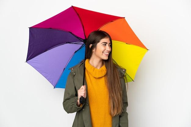 측면을 찾고 흰색 배경에 고립 된 우산을 들고 젊은 여자