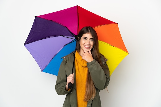 흰색 배경에 고립 된 우산을 들고 젊은 여자가 측면을 찾고 웃고