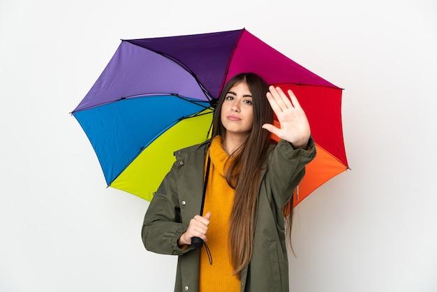 중지 제스처를 만드는 흰색 배경에 고립 된 우산을 들고 젊은 여자