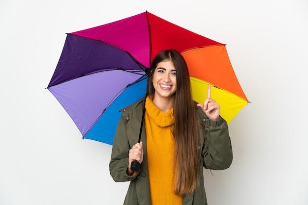 좋은 아이디어를 가리키는 흰색 배경에 고립 된 우산을 들고 젊은 여자