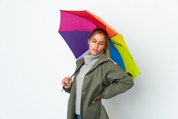 Молодая женщина, держащая зонтик на белом фоне страдает от боли в спине за то, что приложила усилия