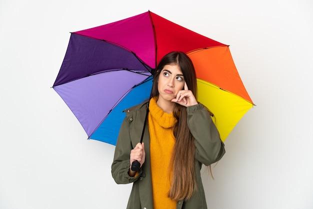 Молодая женщина, держащая зонтик, изолированные на белом фоне, думает об идее