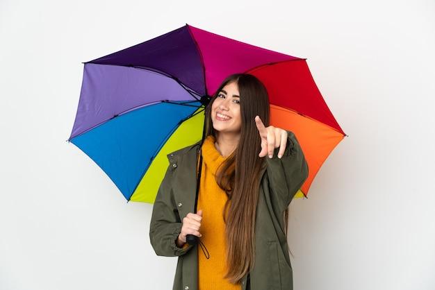 Молодая женщина, держащая зонтик, изолированная на белой поверхности, указывая спереди с счастливым выражением лица