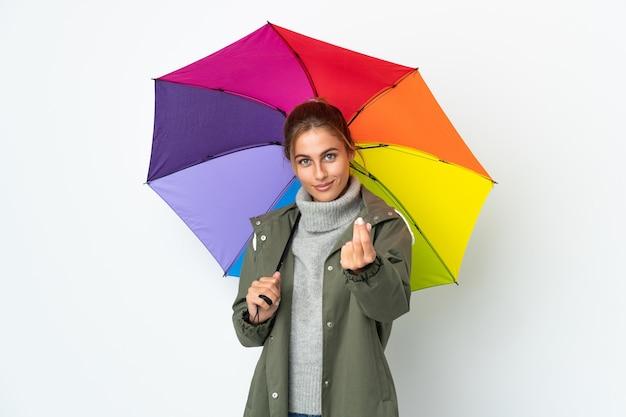 Молодая женщина, держащая зонтик позирует изолированной у глухой стены