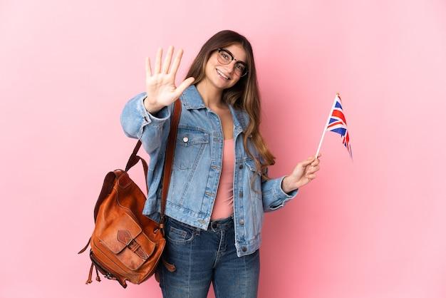 ピンクの背景に分離されたイギリスの旗を持っている若い女性が指で5を数える
