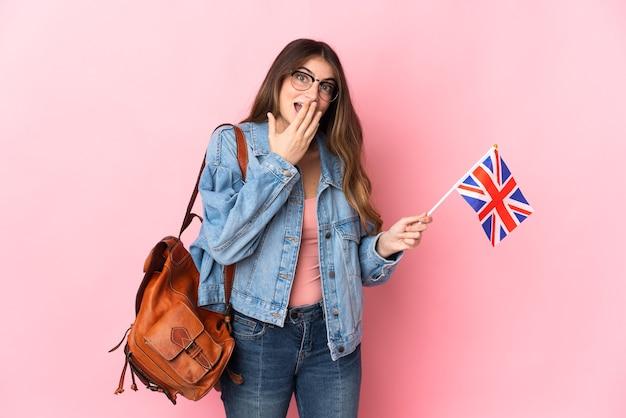 ピンクの幸せと笑顔の手で口を覆って分離されたイギリスの旗を保持している若い女性