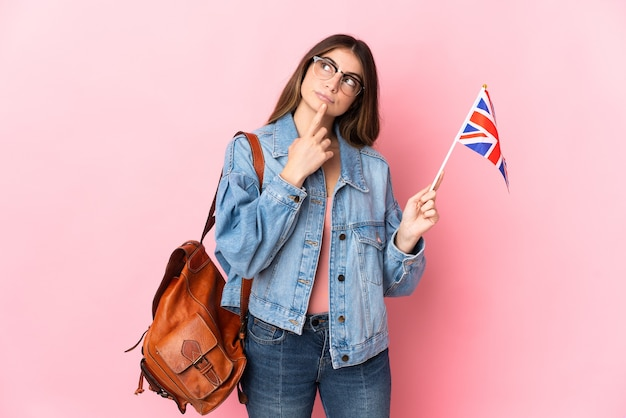 見上げている間疑いを持ってピンクで隔離のイギリス国旗を保持している若い女性