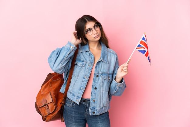 疑いを持ってピンクに分離されたイギリスの旗を保持している若い女性
