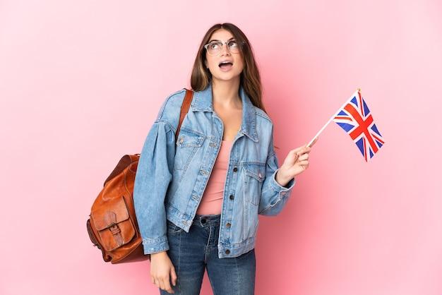 見上げると驚きの表情でピンクに分離されたイギリスの旗を保持している若い女性