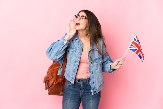 横に大きく開いた口でピンクの叫びで隔離のイギリス国旗を保持している若い女性