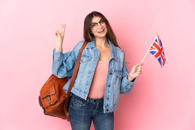 ピンクの笑顔で隔離され、勝利のサインを示すイギリスの旗を保持している若い女性
