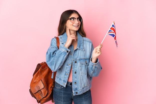見上げながらアイデアを考えてピンクで隔離のイギリス国旗を保持している若い女性