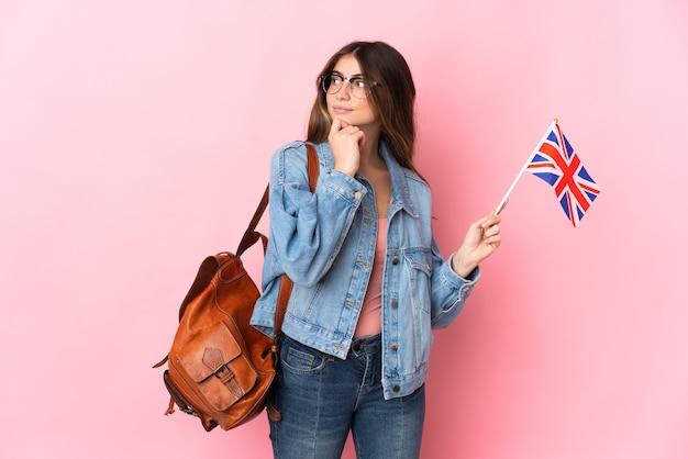 ピンクの壁に隔離され、見上げるイギリスの旗を保持している若い女性