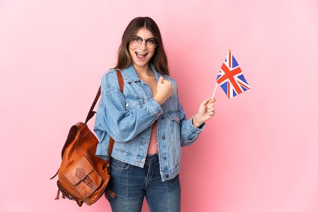 勝利を祝うピンクの壁に分離されたイギリス国旗を保持している若い女性