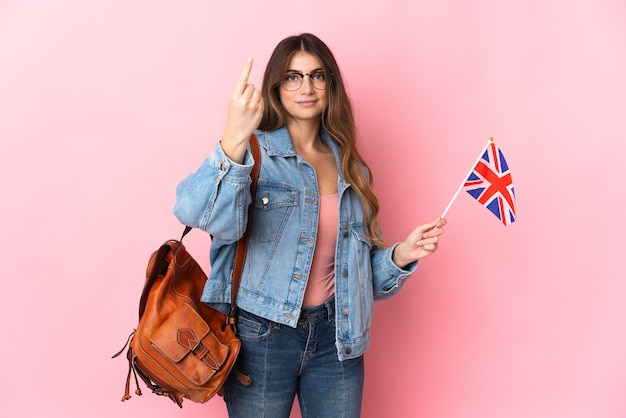 来るジェスチャーをしているピンクの壁に分離されたイギリスの旗を保持している若い女性