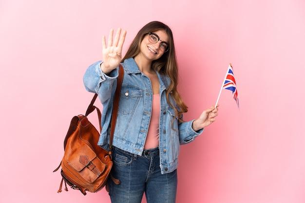 幸せなピンクの壁に分離されたイギリスの旗を保持し、指で4を数える若い女性