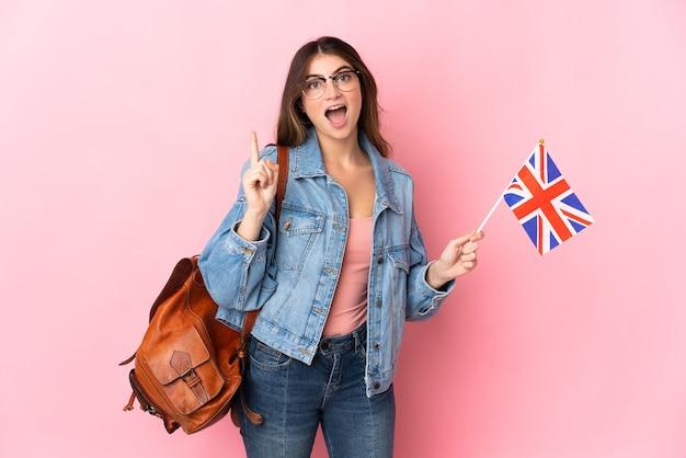 ピンクの壁に隔離されたイギリスの旗を持っている若い女性は、指を持ち上げながら解決策を実現しようとしています
