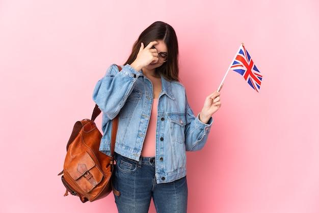 ピンクの壁に分離されたイギリスの旗を持って笑っている若い女性