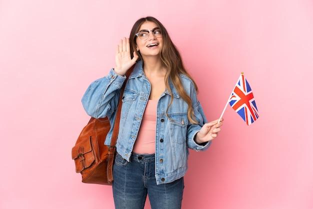 귀에 손을 넣어 뭔가를 듣고 분홍색 벽에 고립 된 영국 국기를 들고 젊은 여자