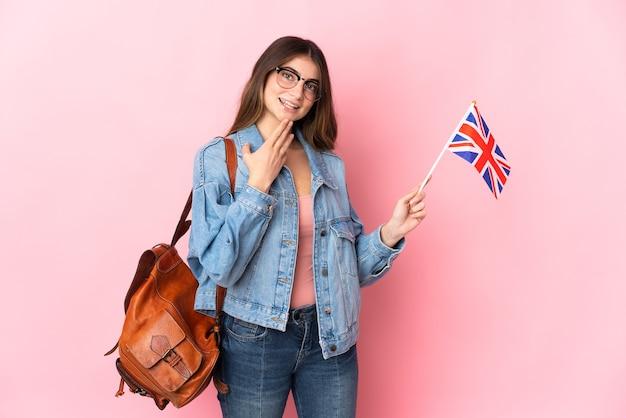 ピンクの壁に分離されたイギリスの旗を持っている若い女性