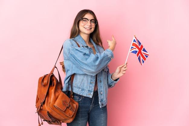後ろ向きのピンクの壁に分離されたイギリスの旗を保持している若い女性