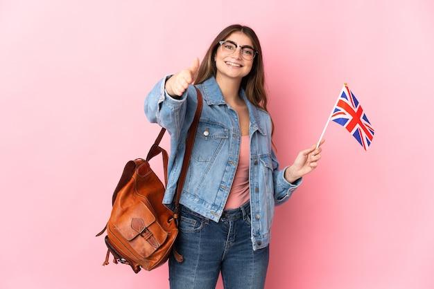 좋은 거래를 닫기 위해 악수하는 분홍색 벽에 고립 된 영국 국기를 들고 젊은 여자