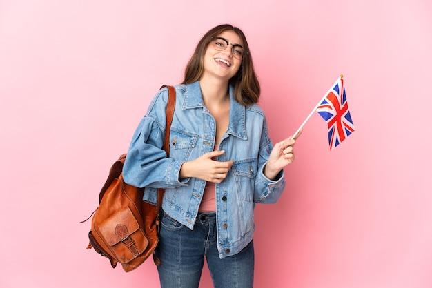 たくさん笑ってピンクの壁に分離されたイギリスの旗を保持している若い女性