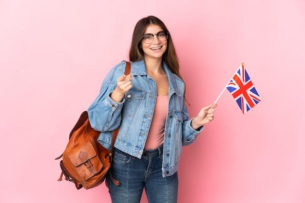 ピンクの壁に分離されたイギリスの旗を持っている若い女性は驚いて正面を指しています