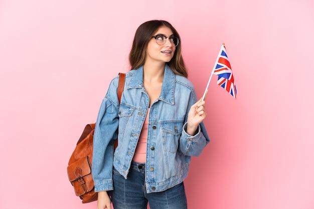 見上げながらアイデアを考えてピンクの壁に分離されたイギリスの旗を保持している若い女性
