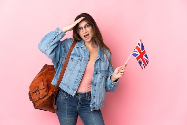 驚きの表情でピンクに分離されたイギリス国旗を保持している若い女性