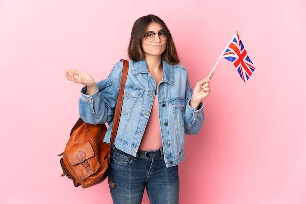 手を上げている間疑いを持っているピンクのイギリス国旗を保持している若い女性