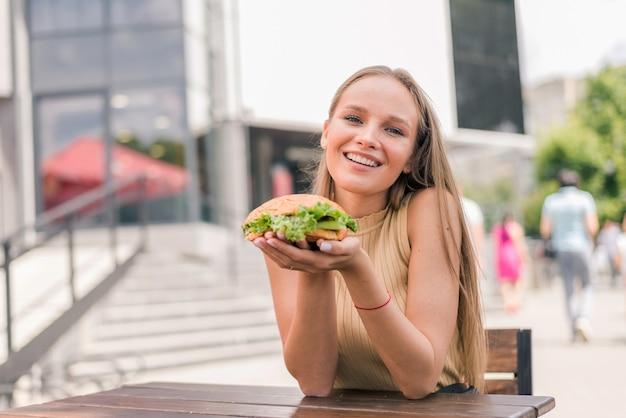 젊은 여자 잡고 카페에서 외부 맛있는 구운 햄버거를 먹는
