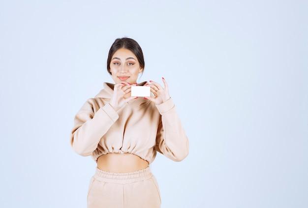 Молодая женщина, держащая и представляя свою визитную карточку Бесплатные Фотографии