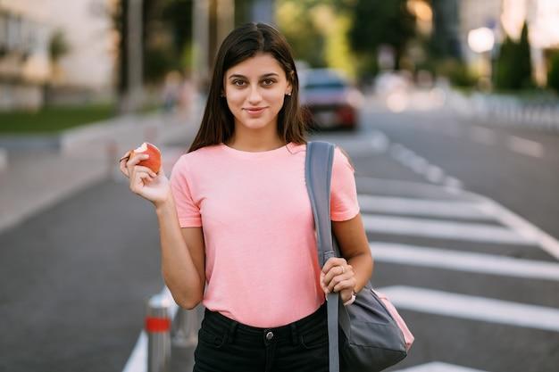 Giovane donna che tiene mela contro uno sfondo di strada