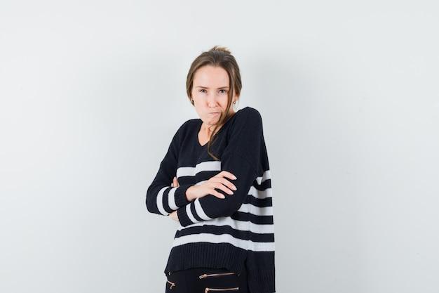 Молодая женщина, держащая скрещенные руки и гримасничающая в полосатом трикотажном белье и черных брюках, выглядит серьезной