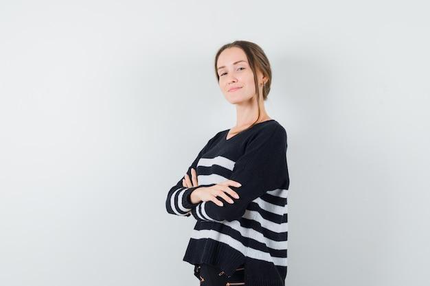 黒のブラウスと黒のズボンで腕を組んで、自信を持って見える若い女性