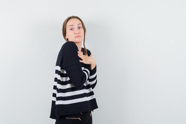 젊은 여자가 팔을 잡고 스트라이프 니트웨어와 검은 색 바지를 입고 가슴을 넘어 놀란 표정