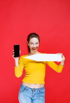 Giovane donna che tiene una freccia che punta a sinistra e uno smartphone nero