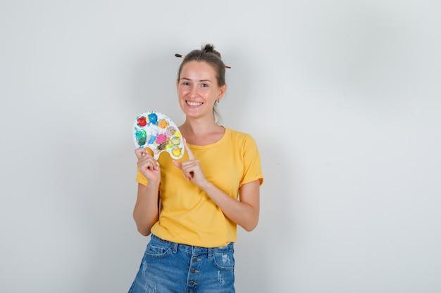 Молодая женщина держит художественную палитру в желтой футболке, джинсовых шортах и выглядит весело