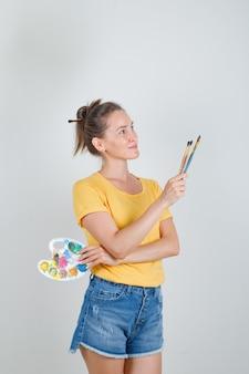 Молодая женщина держит художественную палитру с кистями в желтой футболке, джинсовых шортах и выглядит счастливой