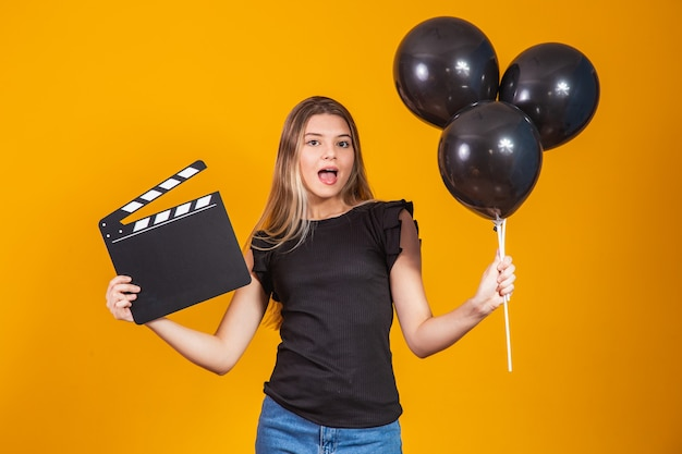 Young woman holding an audio-visual clapper board and black balloons during black friday. promotion concept. black friday