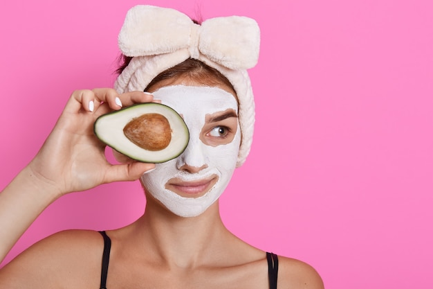 Young woman holding avocado in hands and covering her eyes with fruit, having white mask on face, looking aside, wearing head band with bow isolated over rose background.