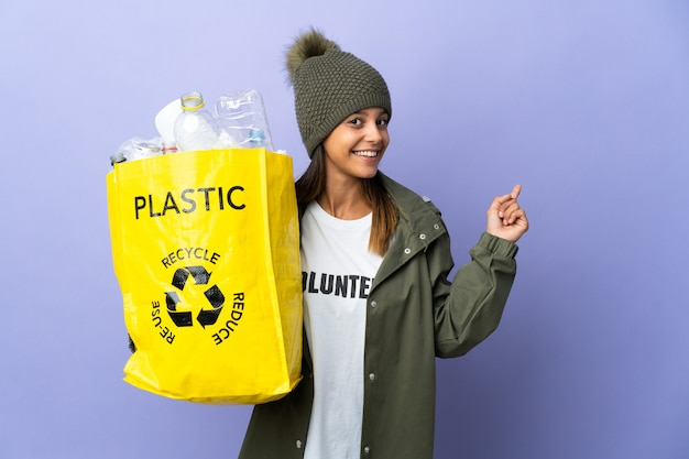Young woman holding a bag full of plastic pointing back