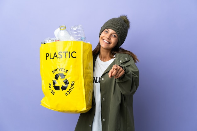 Young woman holding a bag full of plastic pointing front with happy expression