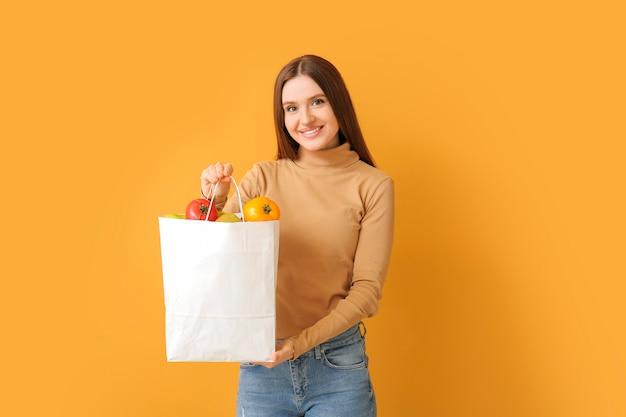 Молодая женщина, держащая сумку с едой на цветной поверхности