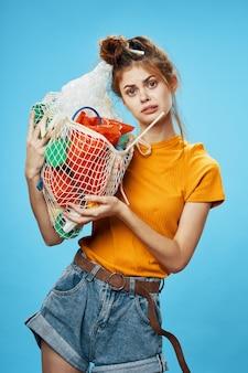 Молодая женщина, держащая мешок с мусором