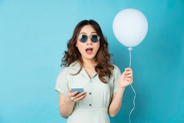 風船を持って、ターコイズで驚きの表情で電話を使用して若い女性